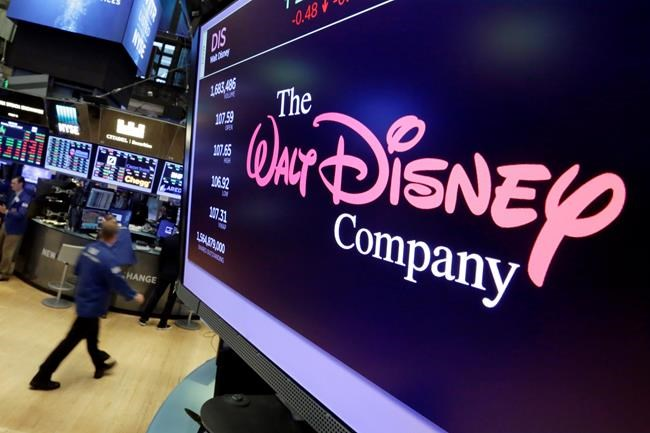 FILE - In this Aug. 8, 2017, file photo, the Walt Disney Co. logo appears on a screen above the floor of the New York Stock Exchange. The Walt Disney Co. reports earnings Thursday, Nov. 8. (AP Photo/Richard Drew, File)