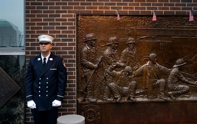 A New York City firefighter stands at attention in front of a memorial on the side of a firehouse adjacent to One World Trade Center and the 9/11 Memorial site during ceremonies on the anniversary of 9/11 terrorist attacks in New York on Tuesday, Sept. 11, 2018. (AP Photo/Craig Ruttle)