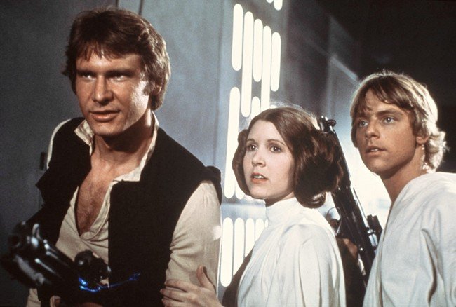 """FILE - This 1977 file image provided by 20th Century-Fox Film Corporation ahows, from left, Harrison Ford, Carrie Fisher, and Mark Hamill in a scene from """"Star Wars."""" Fisher says she's coming back as Princess Leia for the new """"Star Wars"""" films. The actress confirmed that she'll return as the iconic character in an interview posted Wednesday, March 6, 2013, with Florida's Palm Beach Illustrated. Casting for the films has yet to be announced, but Fisher answered a simple """"yes"""" when asked if she would be reprising Leia. (AP Photo/20th Century-Fox Film Corporation, file)"""