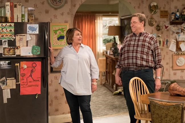 """This image released by ABS shows Roseanne Barr, left, and John Goodman in a scene from the comedy series """"Roseanne."""" ABC's """"Roseanne"""" revival is in the running for Emmy nominations Thursday, but will TV academy voters overlook its star's racist tweet that brought the sitcom to an abrupt end? (Adam Rose/ABC via AP)"""