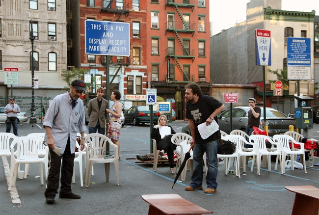 """This July 29, 2013 photo shows actors rehearsing for """"Richard III"""" in a parking lot in New York. Acting in one of Shakespeare's plays is difficult enough without having to dodge a 3,600-pound SUV. The bare-boned but enthusiastic summer production has as many as 77 plastic chairs that are placed in rows around a section of concrete that acts as the stage. If a car needs to get in or out, the actors pause and the patrons pick up their seats and make room. (AP Photo/Mark Kennedy)"""