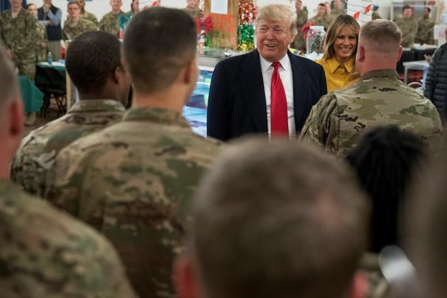 "FILE - President Donald Trump and first lady Melania Trump visit with members of the military at a dining hall at Al Assad Air Base, Iraq. Iran said Wednesday, Jan. 8, 2020, it has launched ""tens"" of surface-to-surface missiles at Iraq's Ain Assad air base housing U.S. troops over America's killing of a top Iranian general. (AP Photo/Andrew Harnik, File)"