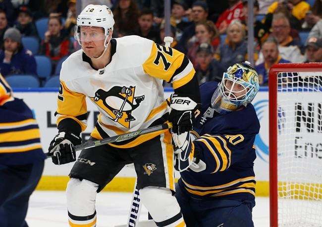 Buffalo Sabres goalie Carter Hutton (40) is screened by Pittsburgh Penguins forward Patric Hornqvist (72) during the second period of an NHL hockey game Thursday, March 14, 2019, in Buffalo, N.Y. (AP Photo/Jeffrey T. Barnes)