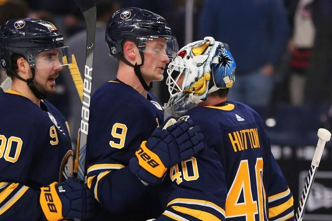 Buffalo Sabres forward JAck Eichel (9) and goalie Carter Hutton (40) celebrate a 2-1- victory following the overtime period of an NHL hockey game against the Columbus Blue Jackets, Saturday, Feb. 1, 2020, in Buffalo, N.Y. (AP Photo/Jeffrey T. Barnes)