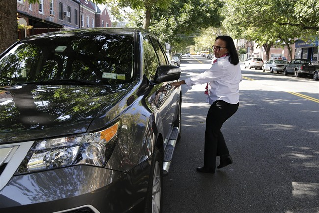 Dinorah De Cruz gets into her livery car after a visit to a Taxi and Limo Commission brokerage, Monday, Sept. 15, 2014, in New York. De Cruz is one of 100 women currently signed up to drive for SheRides, a car service by women drivers for women riders in New York City, Westchester County and Long Island. Less than 3 percent of the city's 115,000 licensed taxi, livery and limousine drivers are women, and that can be a problem for women who are reluctant to get into a cab alone with a male driver because of safety concerns or religious and social mores. (AP Photo/Julie Jacobson)