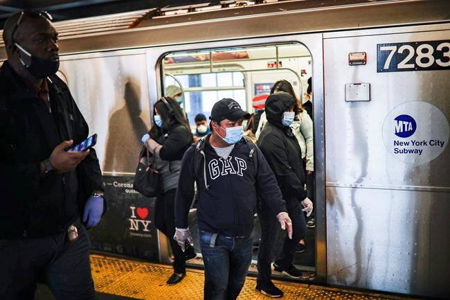 Subway riders, wearing personal protective equipment due to COVID-19 concerns, step off a train, Tuesday, April 7, 2020, in New York. The new coronavirus causes mild or moderate symptoms for most people, but for some, especially older adults and people with existing health problems, it can cause more severe illness or death. (AP Photo/John Minchillo)