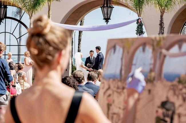 This 2018 photo shows artist Laura Swytak painting during a wedding ceremony at Fess Parker in Santa Barbara, Calif. Some couples are inviting painters to capture a scene or the mood of their big day in a work they can cherish. Having the artist at the reception also adds a special kind of entertainment. (Matt Roberts/Rewind Photography/Laura Swytak via AP)