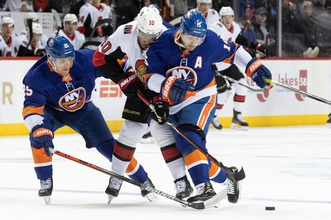 Ottawa Senators left wing Anthony Duclair (10) fights for the puck against New York Islanders right wing Cal Clutterbuck (15) and defenseman Devon Toews (25) during the first period of an NHL hockey game, Tuesday, Nov. 5, 2019, in New York. (AP Photo/Mary Altaffer)