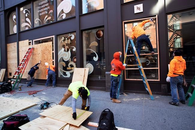 Workers board up windows of a Nespresso store, Monday, June 1, 2020, in the SoHo neighbourhood of New York. Protesters broke into the store Sunday night in reaction to George Floyd's death while in police custody on May 25 in Minneapolis. (AP Photo/Mark Lennihan)