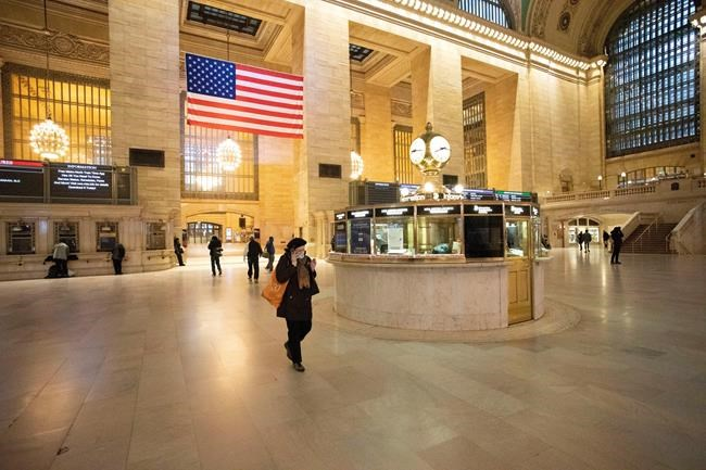 Commuters pass through Grand Central Terminal during the morning rush hour, Monday, March 23, 2020, in New York. Gov. Andrew Cuomo has ordered most New Yorkers to stay home from work to slow the coronavirus pandemic. (AP Photo/Mark Lennihan)