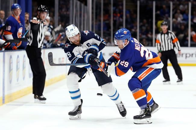 Winnipeg Jets right wing Blake Wheeler (26) passes the puck past New York Islanders center Brock Nelson (29) during the first period of an NHL hockey game Sunday, Oct. 6, 2019, in Uniondale, N.Y. (AP Photo/Michael Owens)