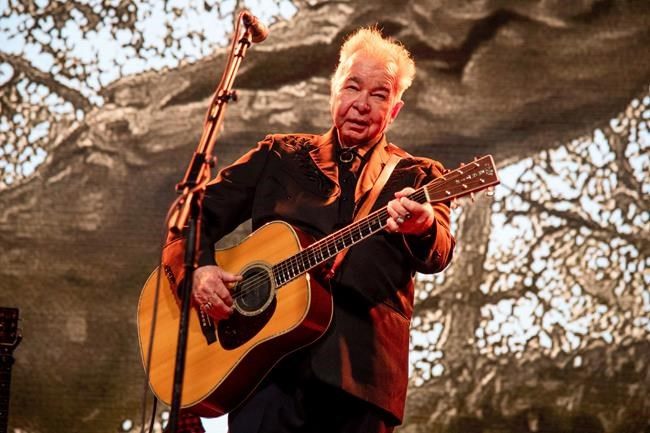 """FILE - This June 15, 2019 file photo shows John Prine performing at the Bonnaroo Music and Arts Festival in Manchester, Tenn. The family of John Prine says the singer-songwriter is critically ill and has been placed on a ventilator while being treated for COVID-19-type symptoms. A message posted on Prine's Twitter page Sunday, March 29, 2020 said the """"Angel from Montgomery"""" singer has been hospitalized since Thursday and his condition worsened on Saturday. (Photo by Amy Harris/Invision/AP, File)"""
