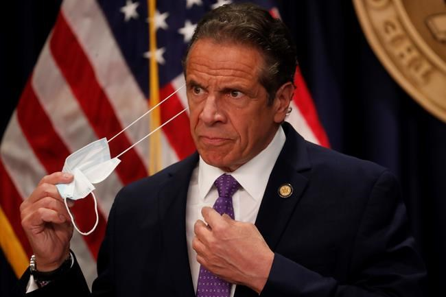 Gov. Andrew Cuomo takes off his face mask before a news conference in New York on Monday, April 19, 2021. Cuomo is allowing more people to go inside museums, movie theaters and indoor big sports arenas as the latest data suggests the state's massive vaccination campaign is curbing COVID-19 infection levels. (Shannon Stapleton/Pool via AP)