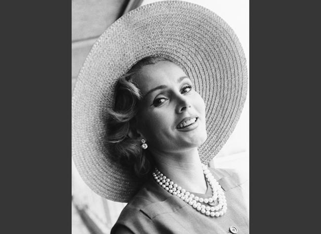 FILE - In a July 14, 1955, file photo, Zsa Zsa Gabor arrives at London Airport from Paris, in a Crimson dress and a straw hat. An auction of late actress Zsa Zsa Gabor's personal items, including scripts, costumes, jewelry and other items has earned more than $909,000. Heritage Auctions said Sunday, April 15, 2018, that the top seller at the two-day auction was a Margaret Keane portrait of the Hungarian-American actress, which sold for $45,000. (AP Photo/File)