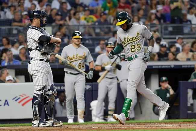 Oakland Athletics' Jurickson Profar, right, runs past New York Yankees catcher Austin Romine to score on a home run during the second inning of a baseball game Friday, Aug. 30, 2019, in New York. (AP Photo/Frank Franklin II)