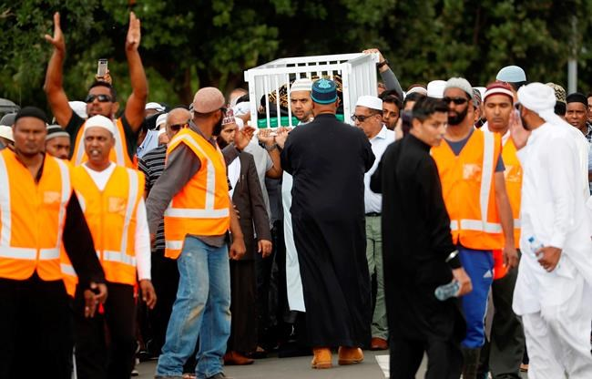 Mourners carry the body of Imam Hafiz Musa Patel, a victim of the Friday March 15 mosque shootings in Christchurch at the Puhinui Memorial Gardens in Auckland, New Zealand, Thursday, March 21, 2019. (Dean Purcell/New Zealand Herald via AP)