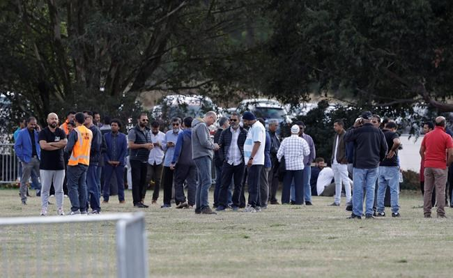 People wait for the start of funeral services in Christchurch, New Zealand, Wednesday, March 20, 2019. The first two burials of the victims from last week's mosque shootings are scheduled to take place Wednesday morning. (AP Photo/Mark Baker)