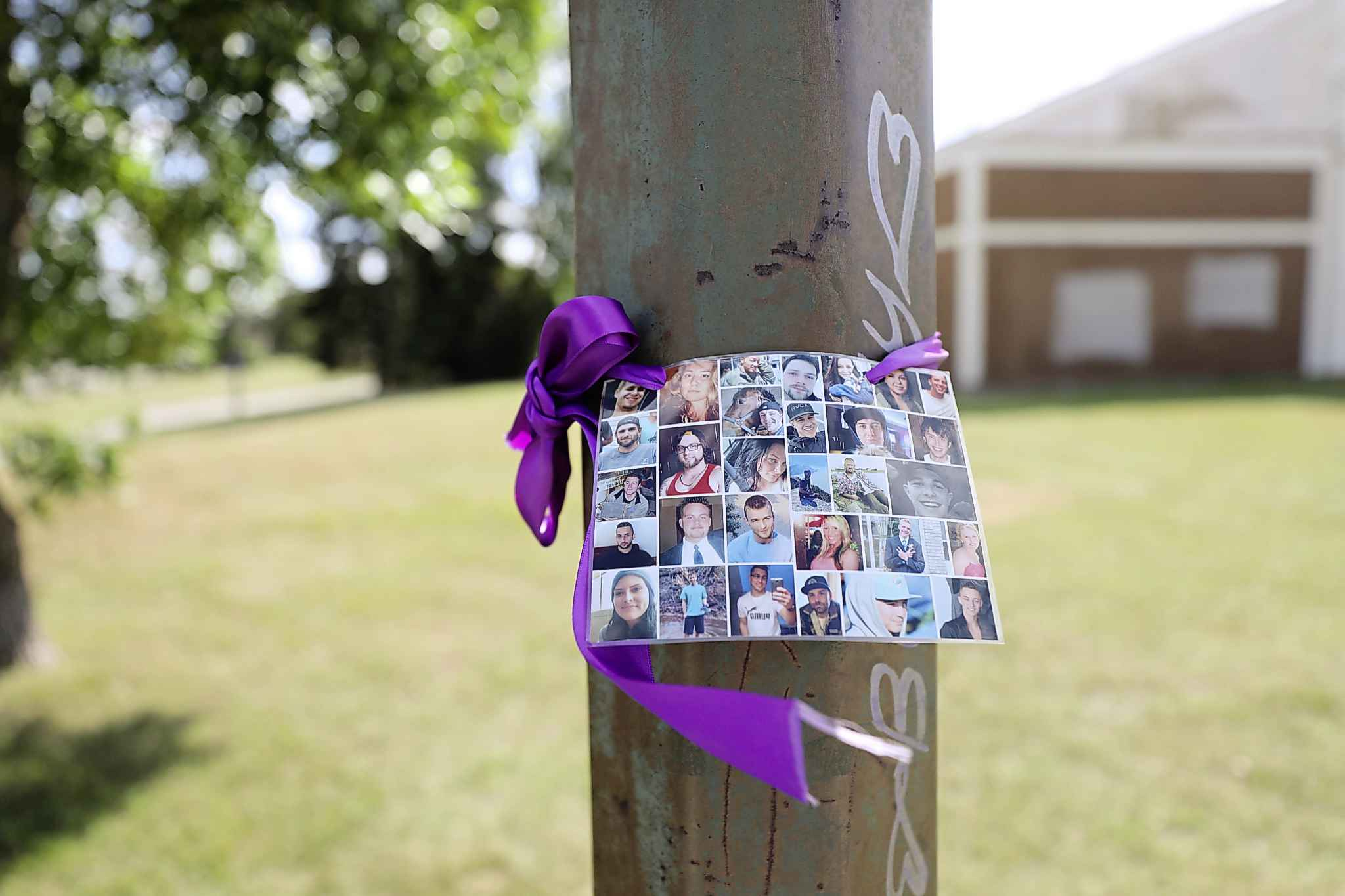 Purple ribbons are placed on door handles and light poles, some with photos of those who lost their lives  to addictions, around the old Vimy Arena.