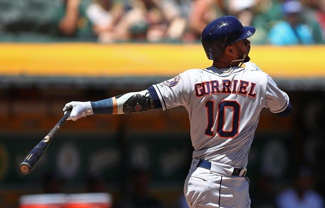 Houston Astros' Yuli Gurriel swings for an RBI double off Oakland Athletics' Frankie Montas in the first inning of a baseball game Thursday, June 14, 2018, in Oakland, Calif. (AP Photo/Ben Margot)