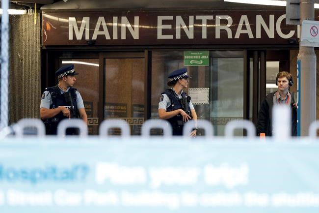 Police stand guard at Christchurch Hospital, which is under lockdown, after mass shootings at two mosques in Christchurch, New Zealand, Saturday, March 16, 2019. (AP Photo/Mark Baker)