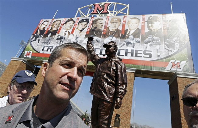 Baltimore Ravens coach John Harbaugh is interviewed next to a statue of him that was unveiled, Saturday, April 19, 2014, at Miami (Ohio) University in Oxford, Ohio, where Harbaugh was inducted into the school's Cradle of Coaches. (AP Photo/Al Behrman)