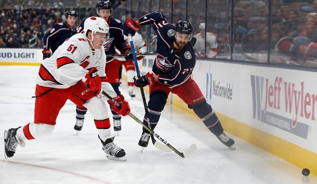 Carolina Hurricanes' Jake Gardiner, left, and Columbus Blue Jackets' Nick Foligno chase the puck during the second period of an NHL hockey game Thursday, Jan. 16, 2020, in Columbus, Ohio. (AP Photo/Jay LaPrete)