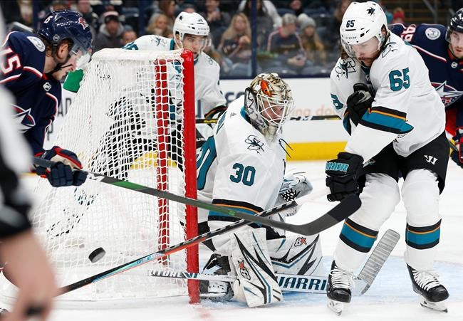 San Jose Sharks' Aaron Dell, center, makes a save between Erik Karlsson, right, of Sweden, and Columbus Blue Jackets' Jakob Lilja, of Sweden, during the second period of an NHL hockey game Saturday, Jan. 4, 2020, in Columbus, Ohio. (AP Photo/Jay LaPrete)