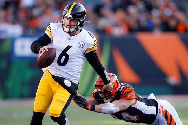 Pittsburgh Steelers quarterback Devlin Hodges (6) runs the ball against Cincinnati Bengals defensive end Sam Hubbard (94) during the second half an NFL football game, Sunday, Nov. 24, 2019, in Cincinnati. (AP Photo/Gary Landers)