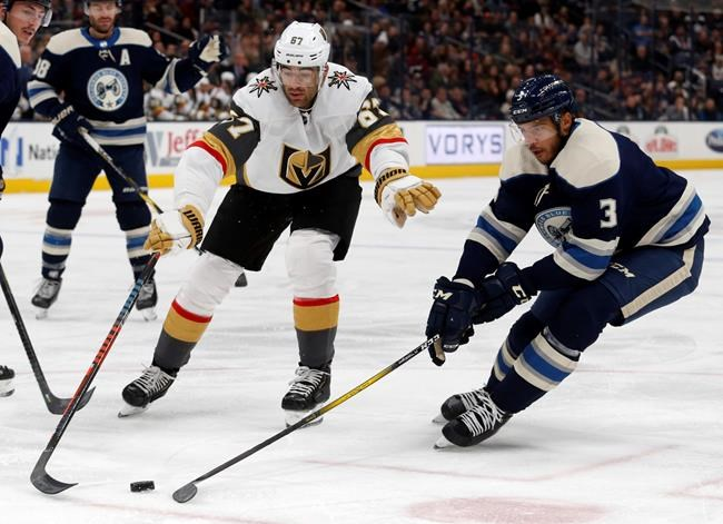 Vegas Golden Knights forward Max Pacioretty, left, reaches for the puck in front of Columbus Blue Jackets defenseman Seth Jones during the first period of an NHL hockey game in Columbus, Ohio, Tuesday, Nov. 5, 2019. (AP Photo/Paul Vernon)