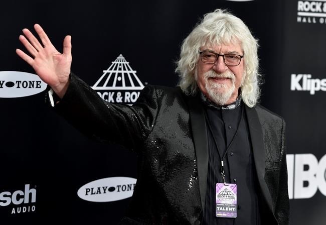Graeme Edge, drummer for the Moody Blues, waves on the red carpet before the Rock and Roll Hall of Fame Induction ceremony, Saturday, April 14, 2018, in Cleveland. (AP Photo/David Richard)