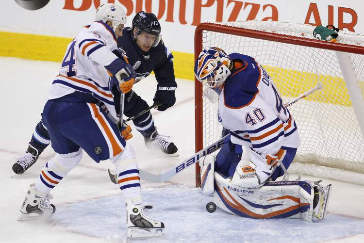 Winnipeg Jets' Kyle Wellwood (13) and Edmonton Oilers' Ryan Smyth (94) fight for position as Oilers' goaltender Devan Dubnyk (40) covers the rebound during first-period NHL action in Winnipeg on Monday.