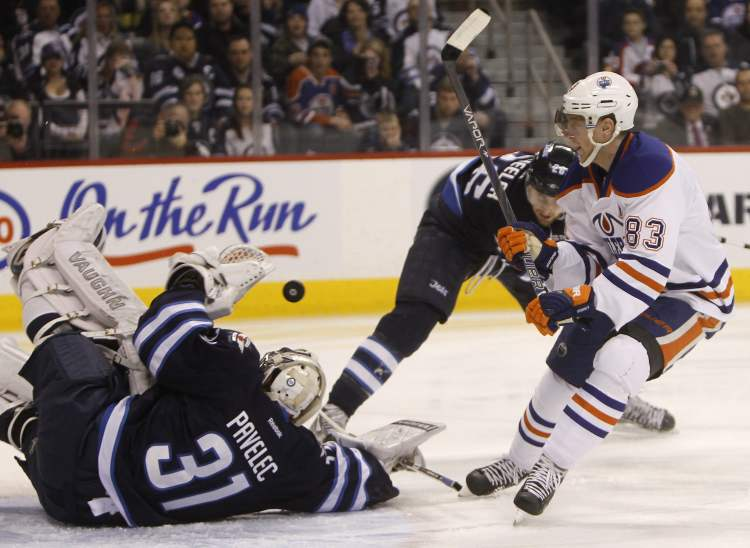 Winnipeg Jets' goaltender Ondrej Pavelec (31) makes a sprawling save on Edmonton Oiler's Ales Hemsky (83) with Jets' Blake Wheeler (26) also in front of the net during first-period NHL hockey action in Winnipeg, Monday.