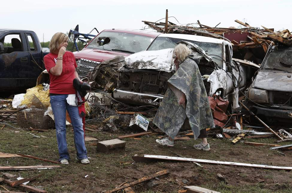 Holly Rictor, left, and her mother Silvia Lee walks past Silvia's tornado-ravaged home in Moore, Okla., on Tuesday. A huge tornado roared through the Oklahoma City suburb Monday, flattening entire neighborhoods and destroying an elementary school with a direct blow as children and teachers huddled against winds.  (Alonzo Adams / The Associated Press)
