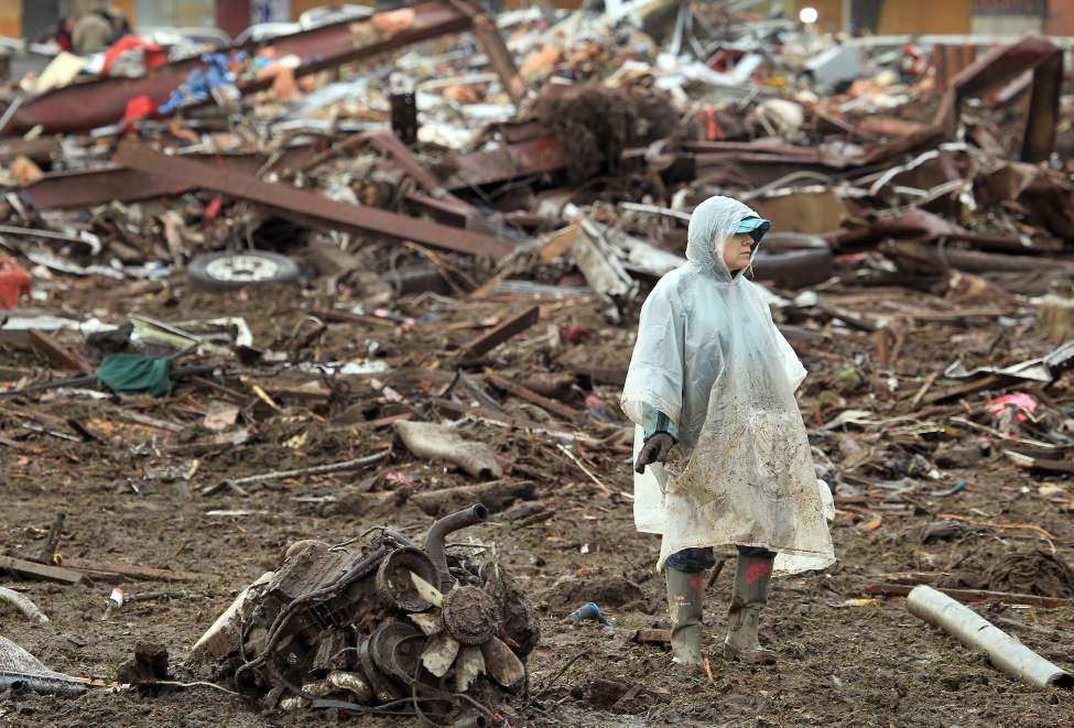 Christine Hammond looks through in the debris behind a friend's home along SW 6th Street in Moore, Okla. looking for personal items on Tuesday.