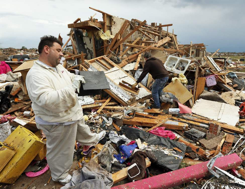 Jon Johnson, left, looks through what is remains of his home at 14716 S. Broadway with his brother Matt Johnson on Tuesday. (Nate Billings / The Oklahoman)