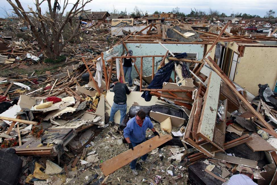 Jimmy Hodges helps Chad Heltcel and his wife Cassidi salvage the wreckage of Chad Heltcel's family home Tuesday.  (Brennan Linsley / The Associated Press)
