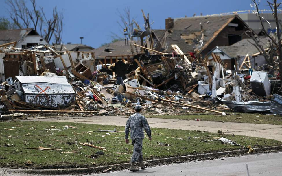 A soldier walks past the wreckage, Tuesday, left when a tornado moved through Moore, Okla. Monday. (Brennan Linsley / The Associated Press)