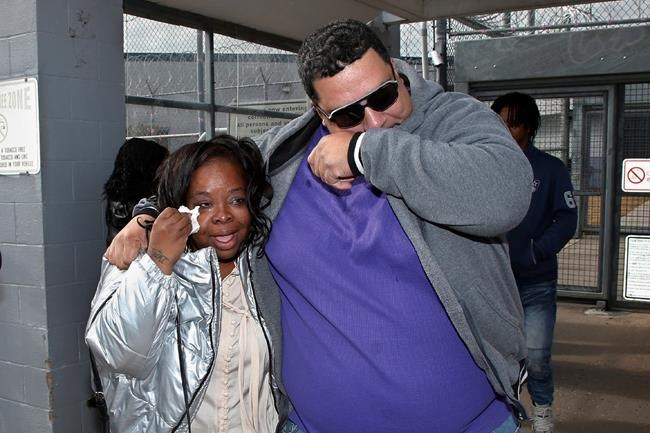 Tondalao Hall, left, and her brother, Jeff Hall, right, wipe tears from their eyes following her release from Mabel Basset Correctional Center in McLoud, Okla., Friday, Nov. 8, 2019. Hall, who was convicted of failing to report her boyfriend for abusing her children, spent about 13 years longer in prison than he did for the abuse. (AP Photo/Sue Ogrocki)