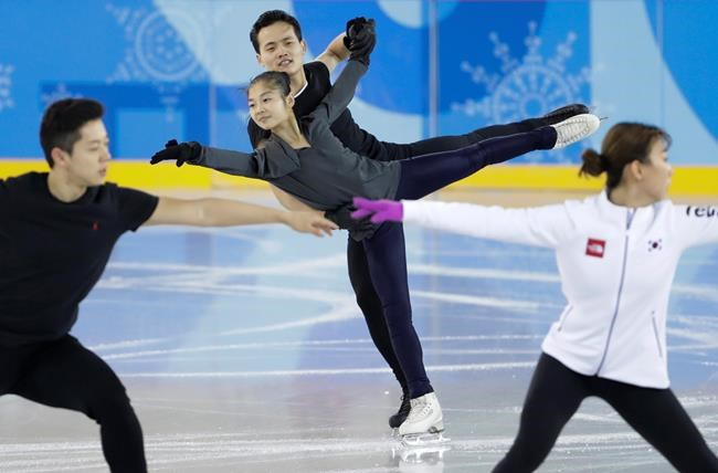 FILE - In this Feb. 5, 2018 file photo, North Korea's Ryom Tae Ok and Kim Ju Sik, center, practice next to South Korea's Kim Kyu-eun, front right, and Alex Kam during a pairs figure skating training session prior to the 2018 Winter Olympics in Gangneung, South Korea. (AP Photo/Felipe Dana, File)