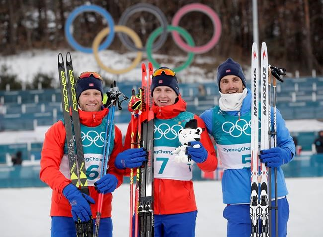 Gold medal winner Simen Hegstad Krueger, of Norway, is flanked by silver medal winner Martin Johnsrud Sundby, of Norway, left, and bronze medal winner Hans Christer Holund, of Norway, after the men's 15km/15km skiathlon cross-country skiing competition at the 2018 Winter Olympics in Pyeongchang, South Korea, Sunday, Feb. 11, 2018. (AP Photo/Dmitri Lovetsky)
