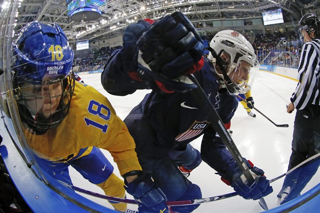 Anna Borgqvist of Sweden and Kacey Bellamy of the United States battle against the glass foe control of the puck during the second period of the 2014 Winter Olympics women's semifinal ice hockey game at Shayba Arena Monday, Feb. 17, 2014, in Sochi, Russia. (AP Photo/Petr David Josek)