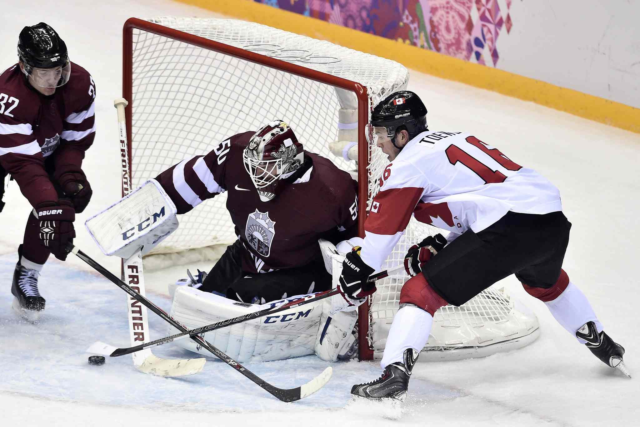 Latvian goaltender Kristers Gudlevskis stymies centre Jonathan Toews on one of 57 Canadian shots on Wednesday night. Team Canada eked out a narrow 2-1 triumph.