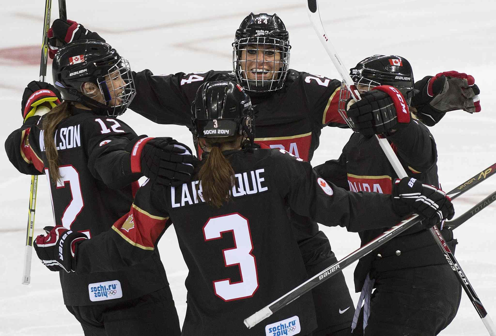 Canada defenceman Jocelyne Larocque (3) celebrates her goal with Canada forward Natalie Spooner, centre, and teammates while playing against Switzerland during first period women's Olympic hockey action at the 2014 Sochi Winter Olympics in Sochi, Russia on Saturday.
