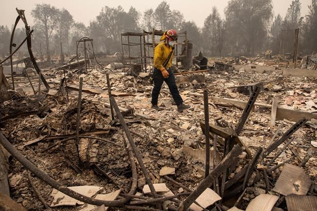 Jackson County District 5 firefighter Captain Aaron Bustard walks through the ruins of a massive fire in a neighborhood to check for smoldering fires as destructive wildfires devastate the region on Friday Sept. 11, 2020, in Talent, Ore. (AP Photo/Paula Bronstein)