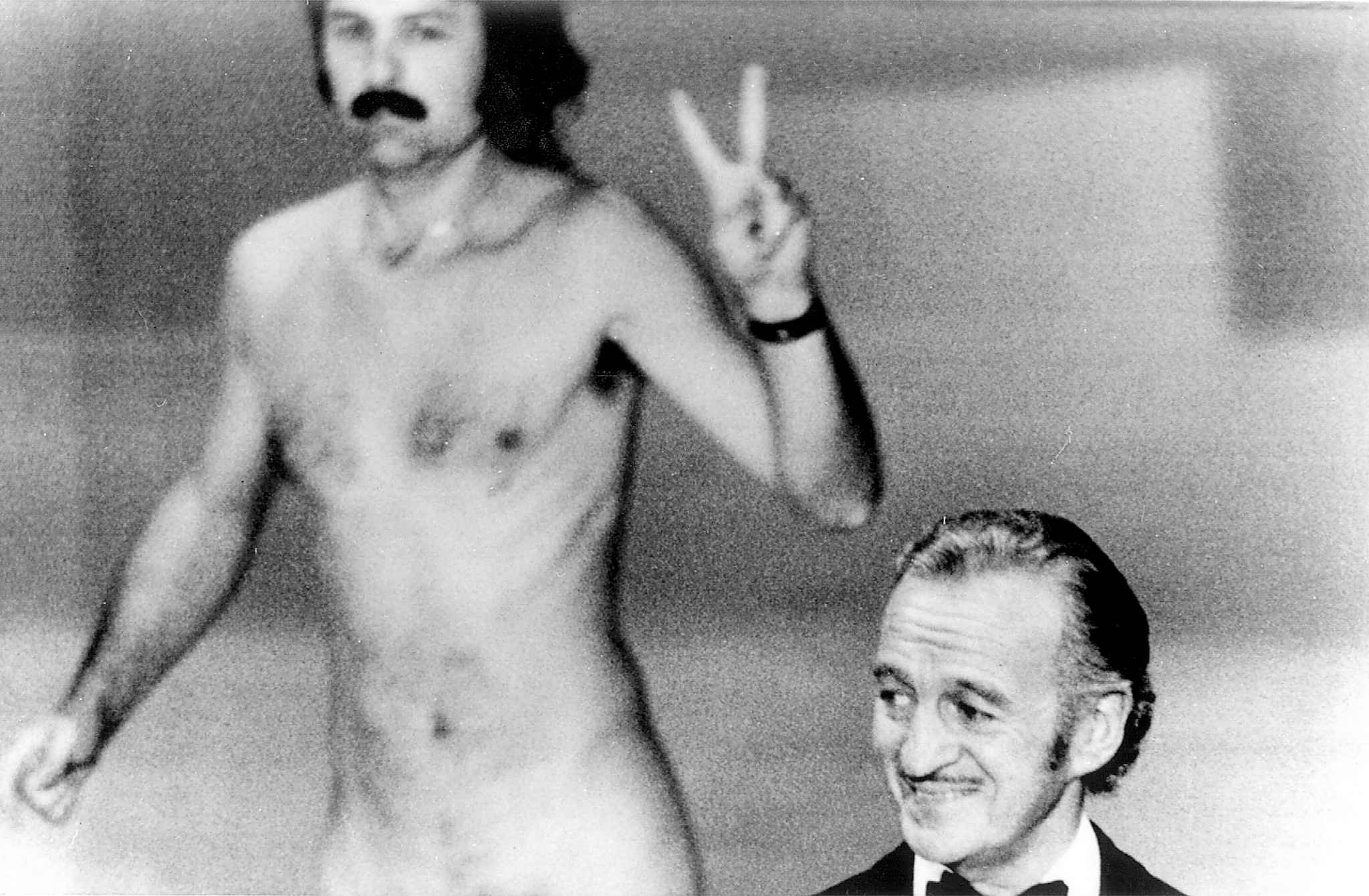 A streaker appears on stage surprising David Niven, right, who isn't quite sure what's happening behind him. (Associated Press files)
