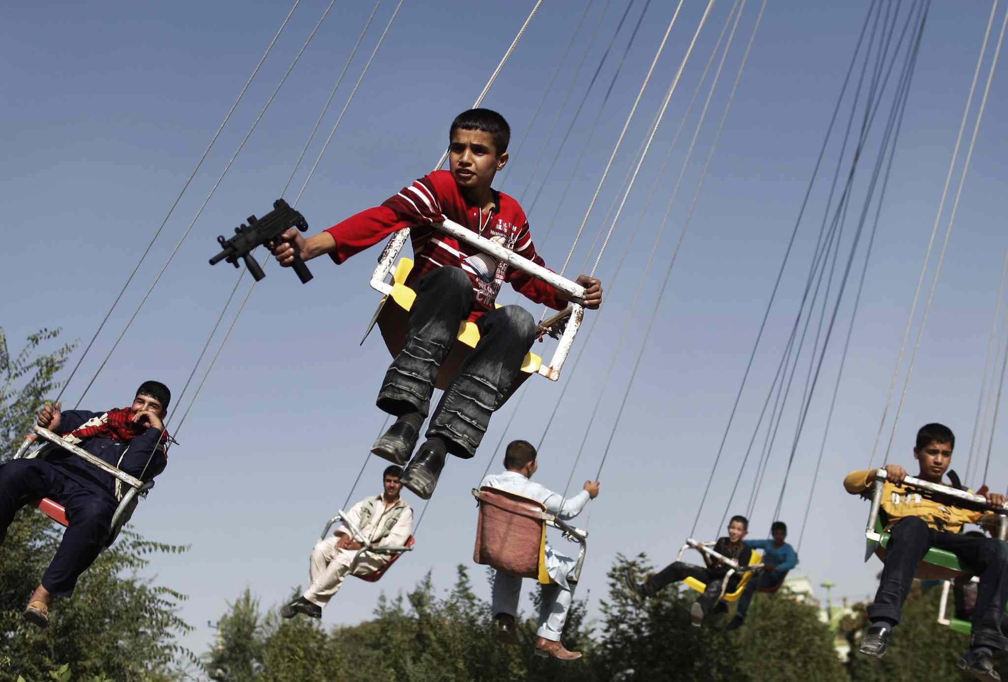 Sept. 20, 2009: An Afghan boy holds a toy gun as he enjoys a ride with others on a merry-go-round to celebrate the Eid al-Fitr festival, in Kabul, Afghanistan.