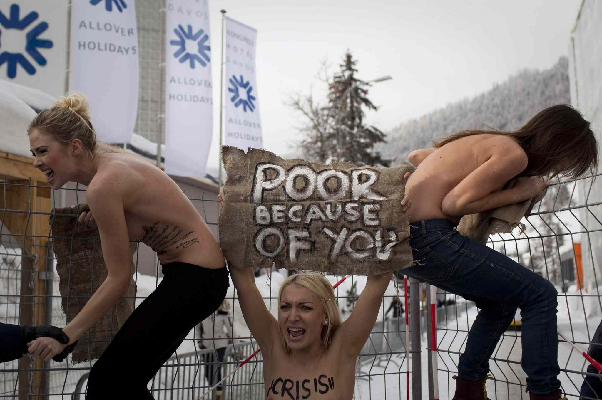 Jan. 28, 2012: Topless Ukrainian protesters climb up a fence at the entrance to the congress center where the World Economic Forum takes place in Davos, Switzerland.