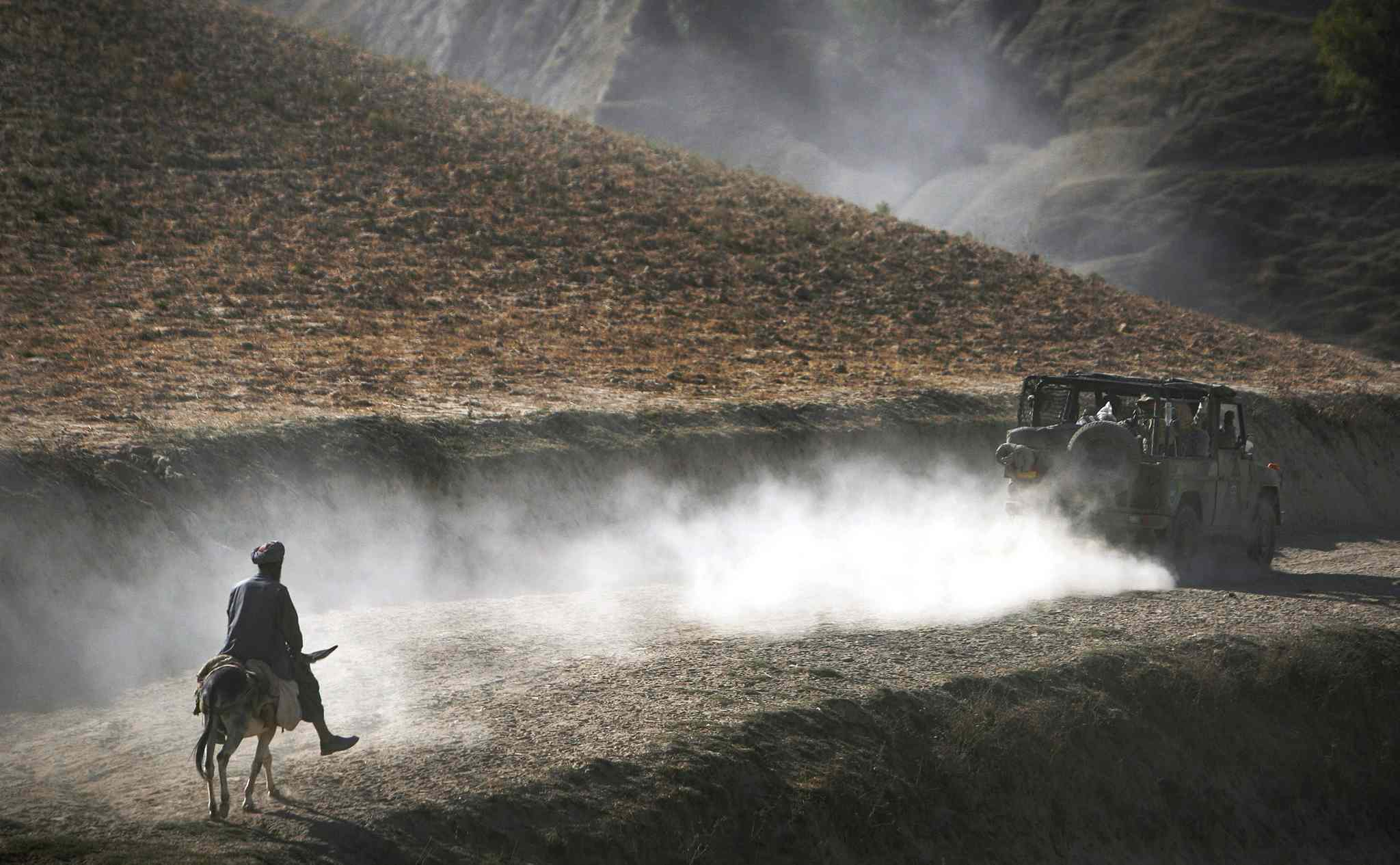 Sept. 15, 2009: An Afghan man on his donkey follows a convoy of German ISAF soldiers patrolling Yaftal E Sofla, in the mountainous region of Feyzabad, east of Kunduz, Afghanistan.