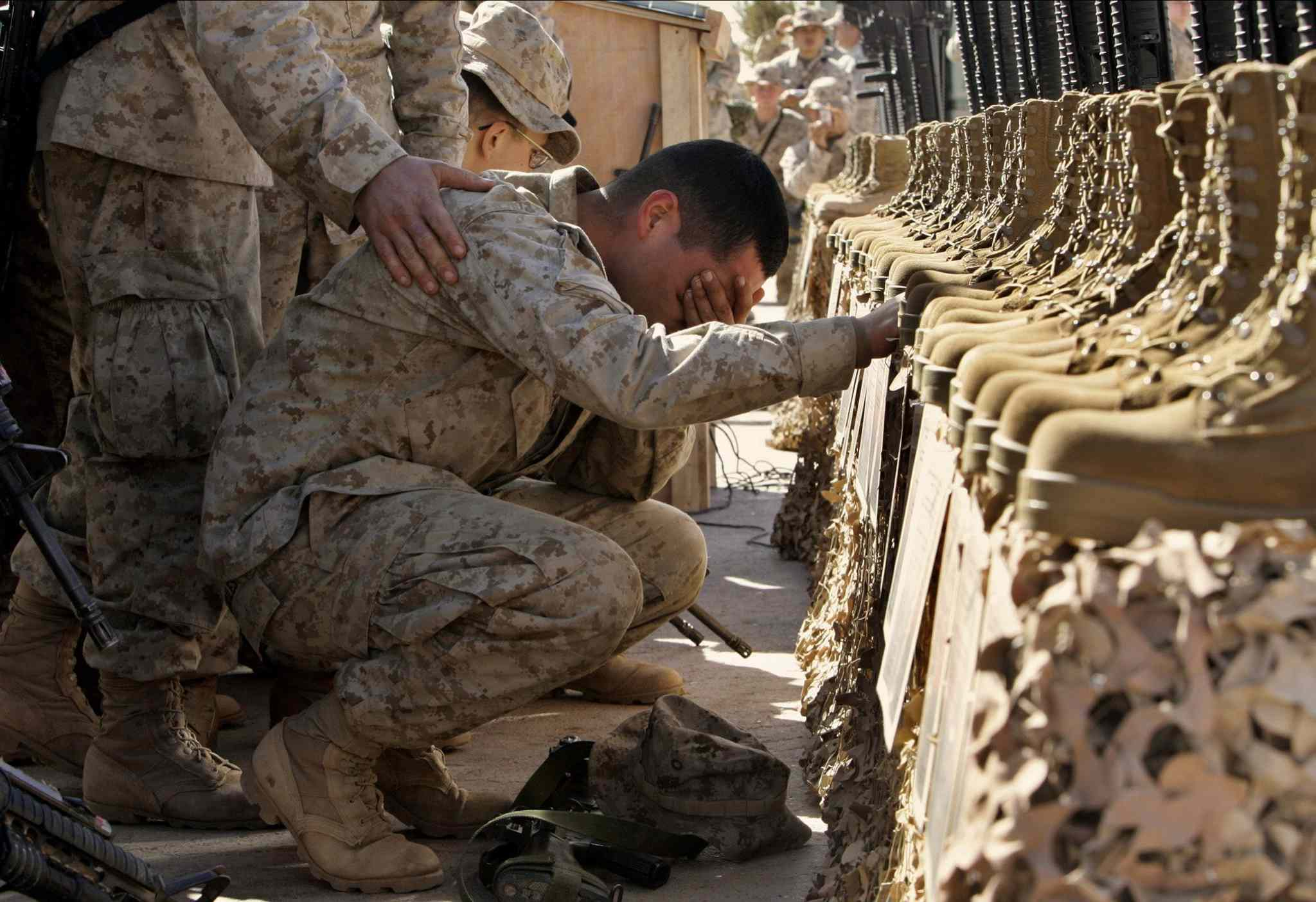 Feb. 2, 2005: A U.S. Marine cries during the memorial service for 31 killed U.S. servicemen at Camp Korean Village, near Rutbah, western Iraq.