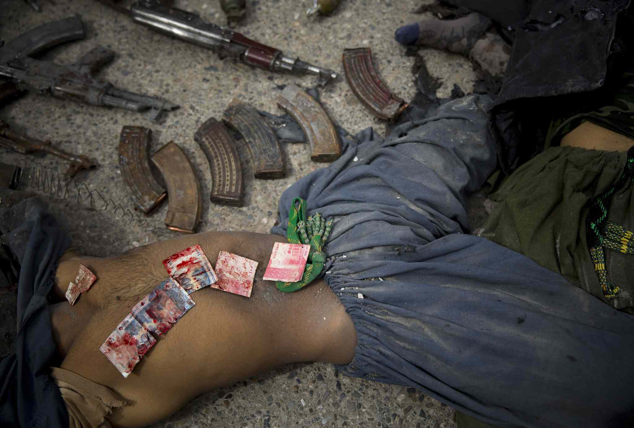 March 12, 2014: Pakistani bank notes covered in blood are displayed on the body of a dead suicide bomber after police found them in his pocket after an attack on the former Afghan intelligence headquarters, in the center of Kandahar, Afghanistan.